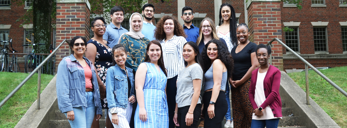 There are three rows of individuals who are the CAM Class of 2019 students standing in front of the Medical-Dental building at Georgetown University.